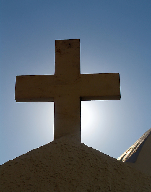 Adobe cross sitting above the peak of an adobe church in Santorini Island, Greece, backlit by the setting sun which highlighs the cross in a quiet blue sky.