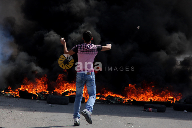 Palestinian youth throws stones at  Israeli border police during clashes at the Kalandia checkpoint near the West Bank city of Ramallah October 9, 2009. Palestinian leaders on Thursday called for a one-day general strike and warned of more street protests over Jerusalem, where clashes at the flashpoint al-Aqsa mosque two weeks ago cranked up tensions in the disputed city. Israel is playing down Palestinian warnings that its security tactics risk a new Palestinian uprising. Photo by Issam Rimawi