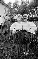ROMANIA / Maramures / Valeni / July 2003..Two teenagers in the wedding party for a young bride pose outside her home...© Davin Ellicson / Anzenberger..