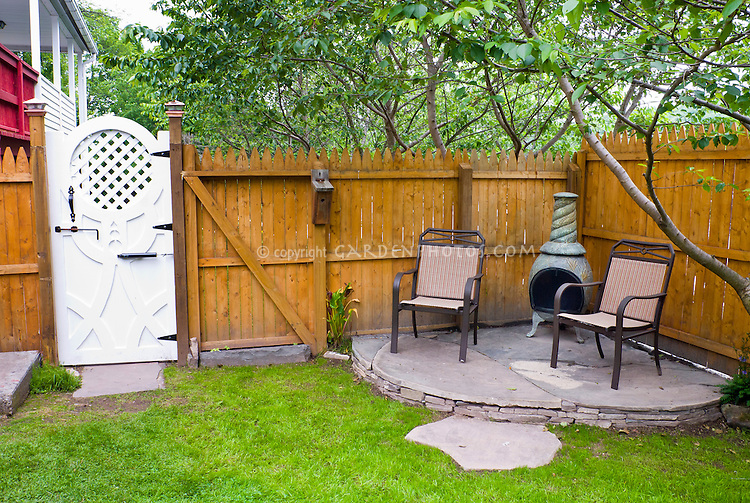 Firepit Bbq Fireplace Outdoors On Small Garden Stone Patio, Wooden Privacy  Fency, Pretty Garden