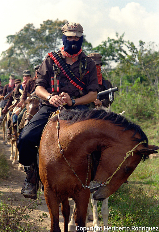 Zapatista Subcomandante Marcos rides horseback as he heads the Zapatista cavalry in their Lacandonian jungle stronghold, March 22, 1994. Zapatista Indian people launched an uprising on January 1st, 1994 opposing to the North American Free Trade Agreement signed by the United States, Mexico and Canada governments. Photo by Heriberto Rodriguez