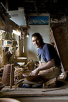 "Portrait of a French potter spinning the clay to make a traditional clay pot or ""cassole"" in which cassoulet is cooked"