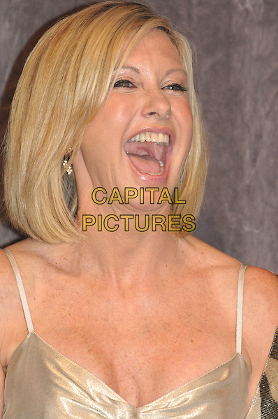 "OLIVIA NEWTON-JOHN .""Score: A Hockey Musical"" Premiere during the 2010 Toronto International Film Festival held at Roy Thomson Hall, Toronto, Ontario, Canada, .9th September 2010..portrait headshot mouth open gold  funny laughing  smiling  .CAP/ADM/BPC.©Brent Perniac/AdMedia/Capital Pictures."
