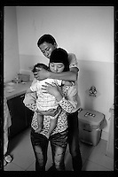 A Muslim couple hugs their son born with cleft lip before an operation organized by Smile Angel Foundation at a hospital in Xining, Qinghai province, China, August 2013. (Names withheld for privacy)