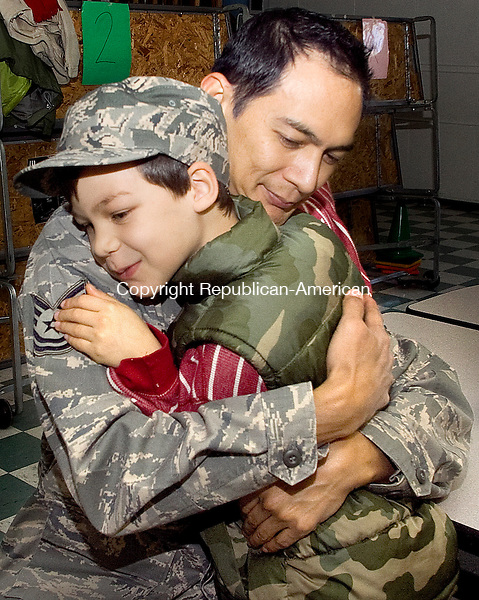 SOUTHBURY CT.-11 NOVEMBER 2010 111110DA01- U.S. Air Force Guardsman Sgt. Peter Reyes of the 159th Fighter Wing, New Orleans hugs his son Jack, 7 of Southbury at Pomperaug Elementary School Thursday. This is the first time that the school is in session on Veterans Day so the students invited veterans, servicemen and women to attend a ceremony in their honor to thank them for their service.<br /> Darlene Douty Republican-American