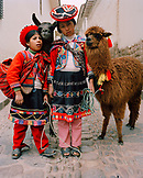 PERU, Cusco, South America, Latin America, girls wearing traditional clothing standing with Llama in a street in Cusco.