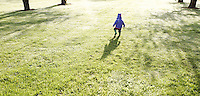 Little girl running through dew coverred grass