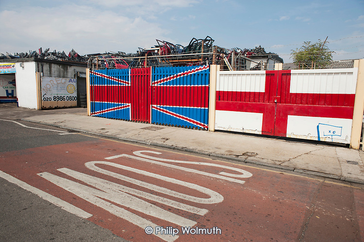Car scrapyard and Union Jack in Hackney Wick.  The rundown area of warehouses, small industrial units and tenement blocks next to the London 2012 Olympic Park has seen a recent influx of young artists attracted by the availability of cheap accommmodation and studio space.