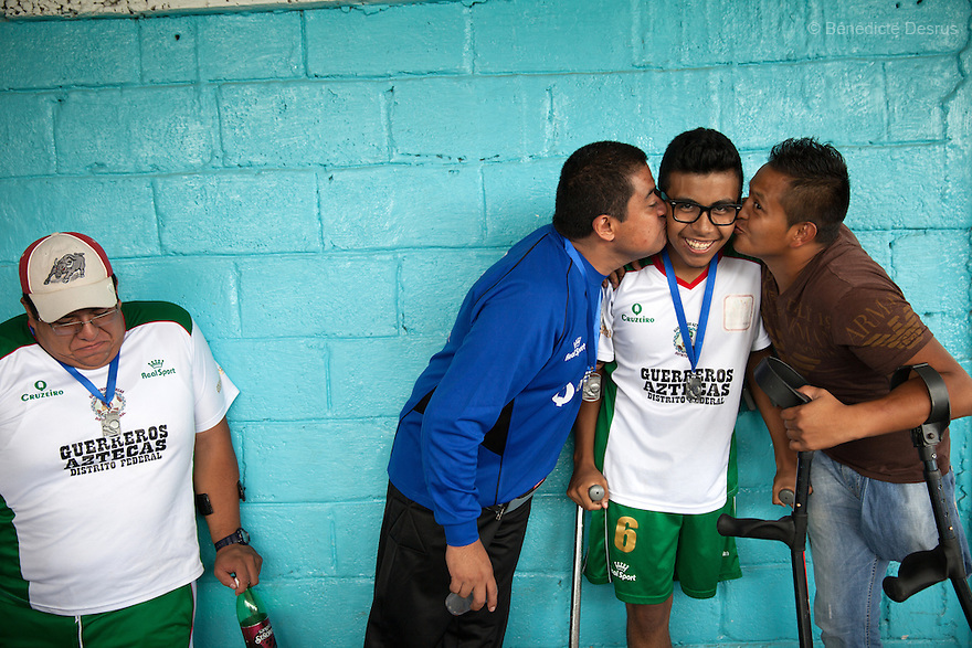 "Baruch with his teammates at Guerreros Aztecas's first anniversary celebrations in Mexico City, Mexico on July 5, 2014. Baruch Alejandro Anleu Ramirez, 18, is the captain of Guerreros Aztecas. Two years ago, Baruch had his left leg amputated due to bone cancer. He used to practice as much as his chemotherapy would allow. Expelled from school for missing too many classes during his treatment, he says, ""Guerreros Aztecas has filled a big hole in my life"". Baruch was Guerreros Aztecas's brightest hope to represent Mexico at the Amputee Soccer World Cup. But since the cancer's spread to his lungs, he can no longer play or train with the team. Guerreros Aztecas (""Aztec Warriors"") is Mexico City's first amputee football team. Founded in July 2013 by five volunteers, they now have 23 players, seven of them have made the national team's shortlist to represent Mexico at this year's Amputee Soccer World Cup in Sinaloa this December. The team trains twice a week for weekend games with other teams. No prostheses are used, so field players missing a lower extremity can only play using crutches. Those missing an upper extremity play as goalkeepers. The teams play six per side with unlimited substitutions. Each half lasts 25 minutes. The causes of the amputations range from accidents to medical interventions – none of which have stopped the Guerreros Aztecas from continuing to play. The players' age, backgrounds and professions cover the full sweep of Mexican society, and they are united by the will to keep their heads held high in a country where discrimination against the disabled remains widespread. (Photo by Bénédicte Desrus)"