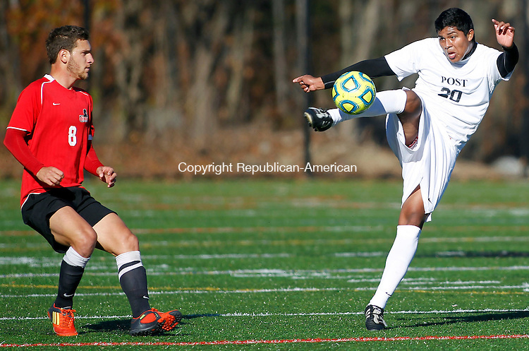 Waterbury, CT-04 November 2012-110412CM08-   Post's Jose Monterroza sends the ball away from Dominican's  Pedro De Araujo  during the CACC championship game Sunday afternoon in Waterbury. Post lost the championship game 3-2 on penalty kicks, after a 1-1 draw during regulation.   Christopher Massa Republican-American