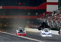 Jun 20, 2015; Bristol, TN, USA; NHRA funny car driver Paul Lee (left) crosses the center line and runs over the foam timing blocks alongside Tony Pedregon during qualifying for the Thunder Valley Nationals at Bristol Dragway. Mandatory Credit: Mark J. Rebilas-USA TODAY Sports