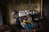 """Ibrahim Toukour, muslimischer Flüchtling in Bangui, Zentralafrikanische Republik, mit seinen Kindern. Die Familie musste vor der Gewalt der der überwiegend aus Christen bestehenden Anti-Balaka-Militia flüchten und lebt in einem Lager am Flughafen. Sie hoffen auf die Ausreise nach Kamerun. Im Hintergrund hat jemand """"Sas Retour de Seleka"""" an die Wand geschrieben - die Seleka-Rebellen werden zurückkehren"""