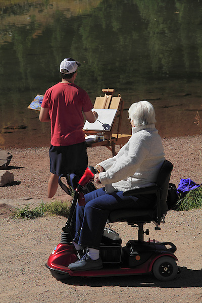 Male artist painting a landscape along lake, disabled senior citizen watches, Rocky Mountain National Park, Colorado. .  John offers private photo tours in Denver, Boulder and throughout Colorado. Year-round Colorado photo tours.