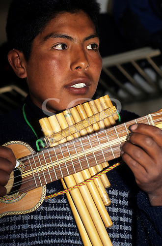 Peru. Musician playing the charango and the panpipes on the train from Puno to Cusco.