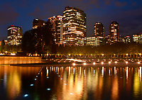 Bellevue's skyline lights up a Reflecting pool in Bellevue Downtown Park at night. Bellevue, Washington.