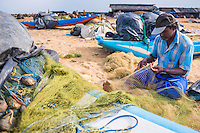Fisherman repairing fishing nets in Negombo fish market (Lellama), Sri Lanka, Asia. This is a photo of a fisherman repairing fishing nets in Negombo fish market (Lellama), Sri Lanka, Asia. Negombo fish market, known as Lellama is the second biggest fish market is Sri Lanka.