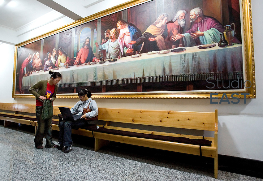 Two young Chinese Koreans check their laptop after a mass, under a painting depicting Jesus' last supper, in the Chinese Christian church of Yanji, Jilin province, China, on May 9, 2009. Photo by Lucas Schifres/Pictobank
