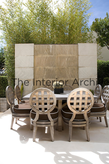 A sheet of water runs down a stone wall that protects an informal outside dining area. The terrace is furnished with a stone topped table and wooden chairs with brown cushion seats with white piping.