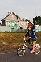 Novy Gorky, Ivanova Region, Russia, 05/08/2012..A woman cycles past a traditional brightly painted Russian wooden home in a settlement near Novy Gorky, some 200 miles east of Moscow.