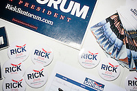 Campaign buttons and stickers lay on a table while former Pennsylvania senator and Republican presidential candidate Rick Santorum speaks at a town hall event put on by the Windham Republican Town Committee at Windham Town Hall in Windham, New Hampshire.