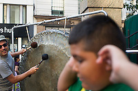 A boy covers his ears while gong players perform in Herald Square in New York  as part of Mass Appeal during the Make Music New York Festival on Friday, June 21, 2012.  Make Music New York, in its 7th year, provides over 1,000 free concerts in public spaces on the first day of Summer. (© Frances M. Roberts)