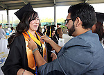 Sergio Arteaga helps graduate Yesenia Pacheco get ready before the Western Nevada College commencement at the Pony Express Pavilion, in Carson City, Nev., on Monday, May 19, 2014. <br /> Photo by Cathleen Allison/Nevada Photo Source