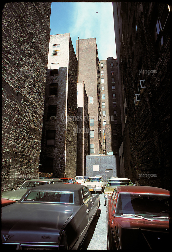 Cadillac and other autos in Alley between Buildings. Brick Side Light with Texture. Brooklyn, New York City, February 25, 1976