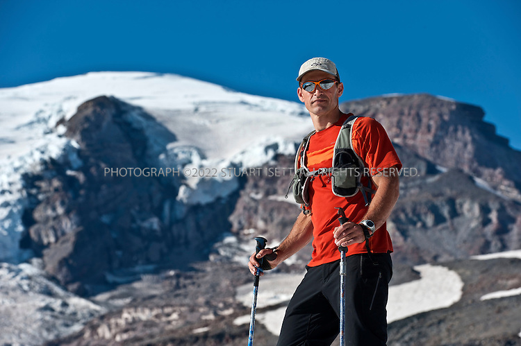 9/14/2011--Mt. Rainier, WA, USA..Chad Kellogg with the summit of Mt. Rainier in the background...Climber Chad Kellogg, 39, training on Mt. Rainier, WASH., for the world speed record climb on Mt. Everest that he will attempt in May, 2012. Kellogg climbs solo and without oxygen...A former competitive luger, Kellogg is a Buddhist who wakes everyday at 4 a.m. to meditate before heading out for training and work. A few years ago, Kellogg had part of his colon removed because of cancer and also lost his first wife to a climbing accident..©2011 Stuart Isett. All rights reserved.