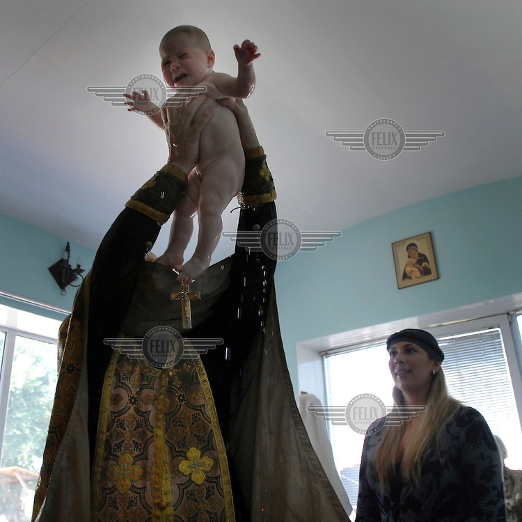 Father Alexander, a Russian Orthodox priest baptises an infant being held by its father in a church.