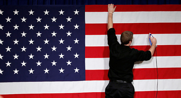 Stage hand RICHIE BEANAN of Milwaukee, Wisconsin irons the American Flag while preparing the Iowa caucus rally site for Republican Presidential hopeful MITT ROMNEY on Tuesday, January 3, 2012 in Des Moines, Iowa.