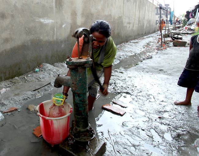 A woman draws water from a well in a slum area near Kolkata, India...Photo by Matt Cashore/University of Notre Dame