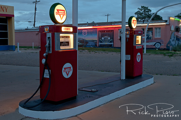 Vintage Conoco gas pumps illuminated at dusk along Route 66 in Tucamcari, New Mexico.