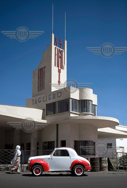 An old but well maintained Fiat car in front of the Fiat Tagliero Service Station in Asmara. Designed by architect Giuseppe Pettazzi and built in 1938, its Futurist Design is in the dynamic form of an aeroplane. The city is a showcase of 1930s Italian Art Deco architecture that was initially brought to the region by colonial-era Italians, the style continued to flourish into the 1960s as local architects furthered the distinctive designs.