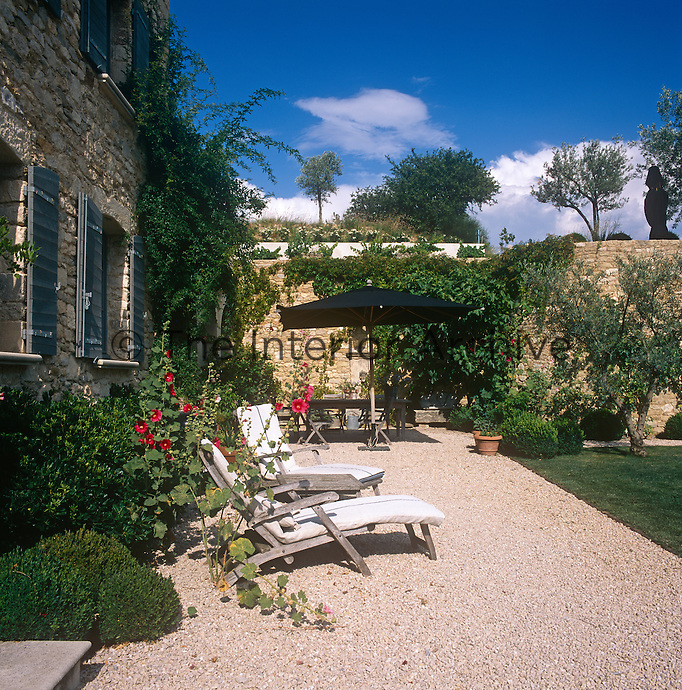 The exterior of a stone country house with sun-loungers and a table and chairs set out on a gravel terrace outside.