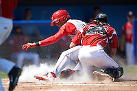 Batavia Muckdogs catcher Blake Anderson (26) tags Jose Pujols (23) sliding into home during a game against the Williamsport Crosscutters on July 16, 2015 at Dwyer Stadium in Batavia, New York.  Batavia defeated Williamsport 4-2.  (Mike Janes/Four Seam Images)