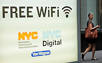 "A woman uses his mobile device next to a poster of Free WiFi in New York, July 15, 2012. New York CIty recently unveiled plans to turn outdated public payphone infrastructure into free WiFi hotspots, according to Mashable. New Yorkers and visitors alike will be able to connect to ""NYC-PUBLIC-WIFI"" using smartphones, tablets, or laptops. local media reported. Photo by Eduardo Munoz Alvarez / VIEW."