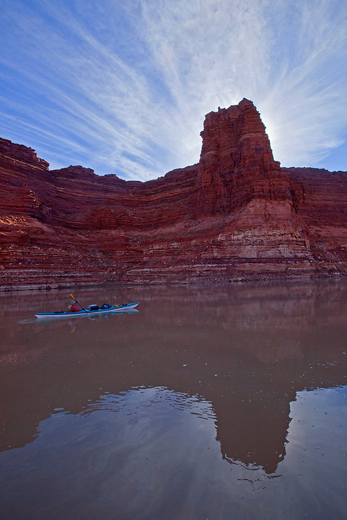 Jacque Miniuk kayaks past striated sandstone cliffs called The Palisades on the Colorado River/Lake Powell in the Glen Canyon National Recreation Area, Utah