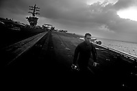 A member of the crew walks on the flight deck of the USS Dwight D. Eisenhower (CVN 69), a nuclear powered american aircraft carrier that is currently supporting Operation Enduring Freedom, the american effort in Afghanistan, by sending tens of its jets every day to support ground troops in air to ground bombing operations, on Monday June 1 2009 at an undisclosed location in the Arabian Sea.