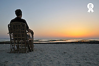 Man on chair watching sunrise over sea, Red Sea, Egypt (Licence this image exclusively with Getty: http://www.gettyimages.com/detail/81865729 )