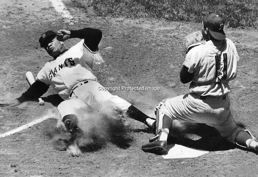 Sam Francisco Giants Felipe Alou slides into home beating the throw to Philadelphia Phillies catcher Clay Dalrymple . (1962 photo/Ron Riesterer)
