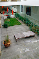 Aerial view looking down on the paved inner courtyard garden which is surrounded by plate-glass windows