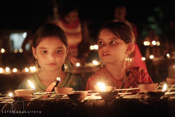 Twin girls lighting the deyas,Hindu Festival of Lights, Divali