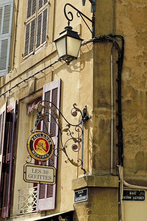 Ornate sconce sign for Les 30 Gouttes Restaurant also advertising Paulaner beer. Sconce streetlamp. Lavender shutters and low wrought iron window grill painted white. Street name placards. Aix en Provence Provence France.