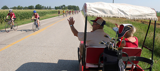 Kesley area farmer Dick Schurman drives a golf cart with Hattie LaRue to greet RAGBRAI riders leaving Kesley Wednesday.