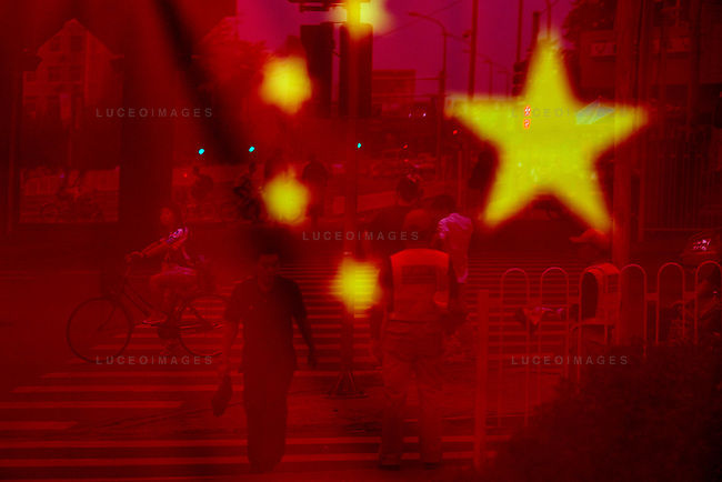 A street scene is reflected off a Chinese flag in a restaurant window in Beijing, China on Wednesday, August 20, 2008.  Kevin German