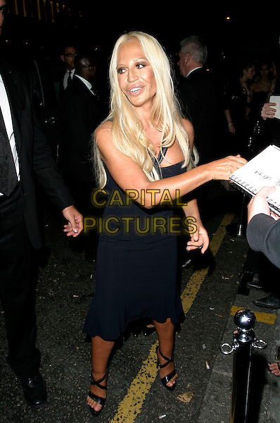DONATELLA VERSACE.Launch party for the 21st anniversary issue of Elle Magazine at the Versace Store in Sloane Street, London, UK..September 7th, 2006.Ref: AH.full length black dress signing autograph.www.capitalpictures.com.sales@capitalpictures.com.©Adam Houghton/Capital Pictures.