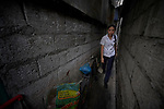 Ella Manio, a student in the Mary Johnston College of Nursing in Manila, walks through the narrow passages in the Parola neighborhood of Manila's Tondo section. Manio and other nursing students regularly visit the neighborhood to do health education and monitor the health of residents. The students also run a feeding program for neighborhood children.<br /> <br /> The nursing school is supported by United Methodist Women.