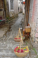 Vegetables for sale in baskets in narrow alley, Hong Cun, Yi County, China