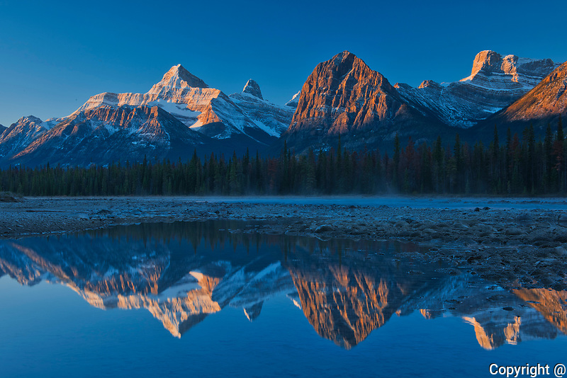 Sunrise on the Canadian Rocky Mountains reflected in the Athabasca River. Icefields Parkway.<br />Jasper National Park<br />Alberta<br />Canada