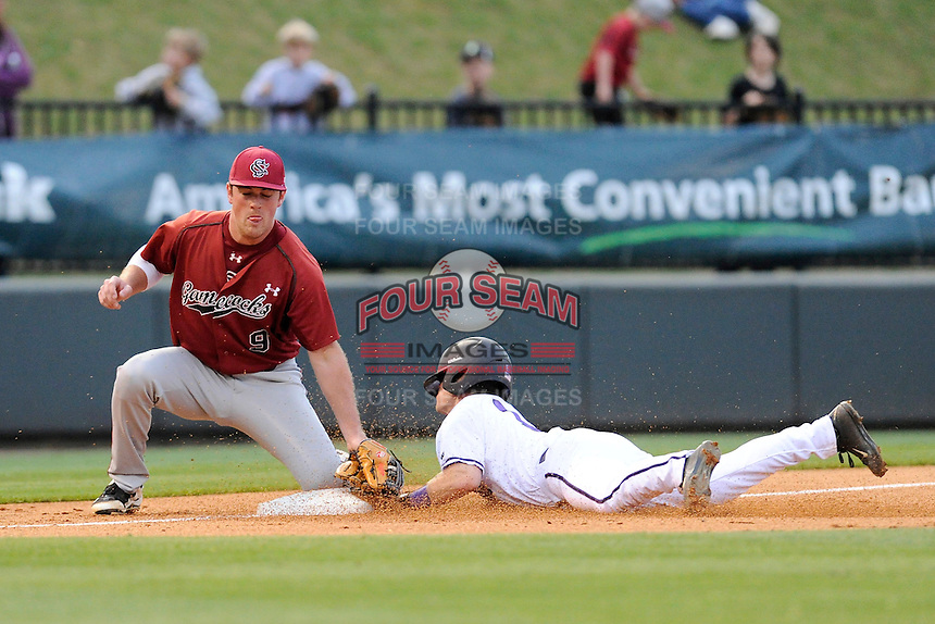 Shortstop Hunter Burton (1) of the Furman Paladins dives in safely at third base as South Carolina Gamecocks third baseman Joey Pankake (9) applies the tag too late in a game on Tuesday, April 8, 2014, at Fluor Field at the West End in Greenville, South Carolina. South Carolina won, 9-2. (Tom Priddy/Four Seam Images)